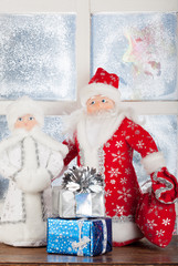 toy Santa Claus, Snow Maiden, present box near frost window