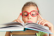 Little girl put fingers on glasses, read book