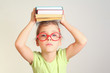 Little girl in glasses hold books on head