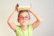 Little girl in glasses hold books on head