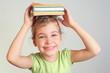 Smiling little girl hold books on head