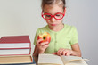 Little girl in glasses eat apple, read book, focus on glasses