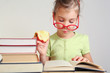 Little girl in glasses eat apple, read book near stack of books