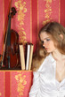 beautiful girl in blouse in room near violin
