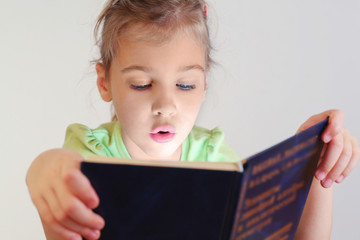 Little blue eyes girl with lighting on face read book