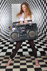 girl  stand in square room, hold old tape cassette recorder