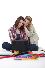 female students sitting on floor with laptop