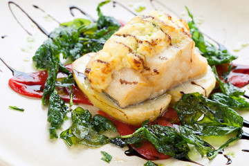 Grilled cod fish with spinach leaves.