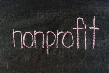 The word NONPROFIT handwritten with chalk  on a blackboard