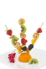 Mini pancake with cut fruits on skewers, isolated.
