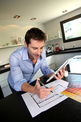 Man looking at house blueprint and choosing paint colours