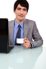Worker drinking coffee in front of laptop