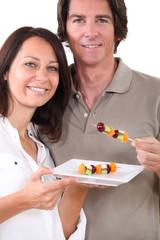 Couple preparing fruit kebabs