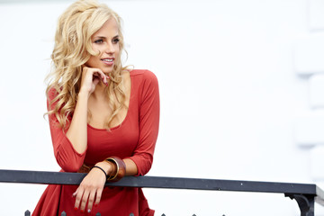 Portrait Of Beautiful Blonde City Woman in red dress
