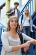 Three students standing on an exterior staircase