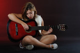 An attractive young girl with an acoustic guitar