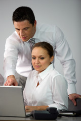 Man explaining something to woman on laptop