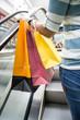 Frau mit Einkaufstüten auf Rolltreppe