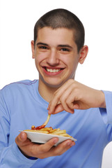 Niño contento comiendo patatas fritas,salsa de tomate.