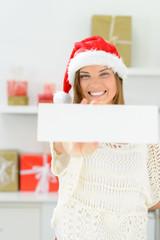 frau mit weihnachtsmütze und hinweisschild