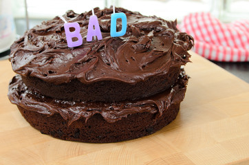 Home made chocolate cake with the word 'Bad' on top