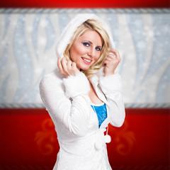 junge blonde Frau im Winteroutfit vor Weihnachtshintergrund
