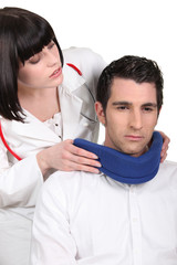 Doctor putting a neck brace on her patient