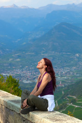 Woman with eyes closed sitting on a ledge.