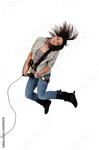 Young woman playing the electric guitar