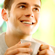 Young happy smiling man with cup of coffee