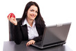 Young businesswoman eating an apple while sitting at office desk