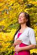Frau im Herbstwald bei Entspannungsübung