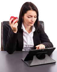 Young businesswoman eating an apple while using a tablet