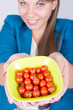 Happy young woman holding a bowl full of cherry tomatoes