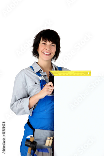 Female carpenter with a board left blank for your copy