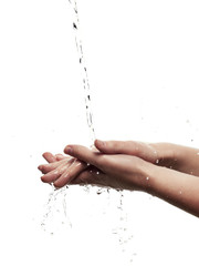Female hands among splashing water - isolated