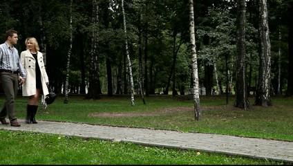 Двое влюблённых идут по дорожке парка