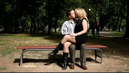 Двое влюблённых целуются на лавочке