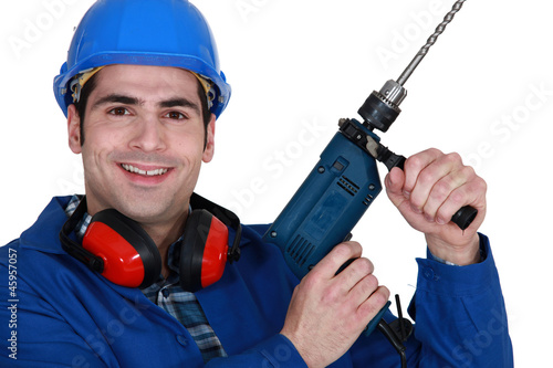 Tradesman holding up an electric screwdriver