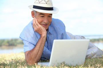 Senior man lying on the grass using a laptop computer