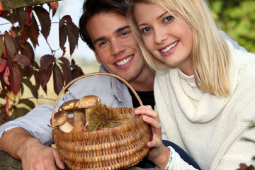 Couple collecting chestnuts and mushrooms in the forest