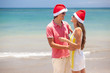 beautiful couple in santa hats on tropical beach of Bali