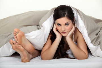 Female and male feet in bed
