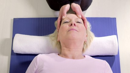 Therapist doing reiki therapy and happy mature woman relaxing
