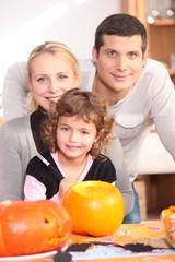 Little girl with parents preparing pumpkin for Halloween
