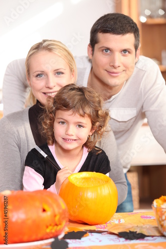 Little girl with parents preparing pumpkin for Halloween