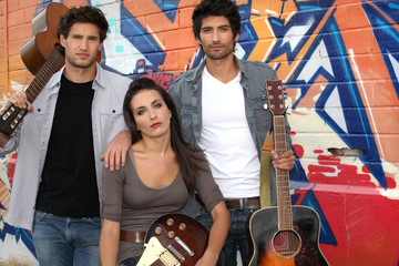 Three musician stood by graffiti