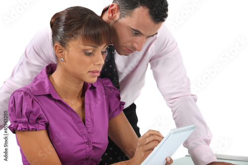 Two businesspeople reviewing notes