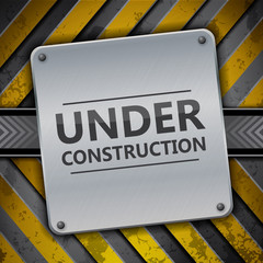 Under construction metal sign on metallic warning stripes