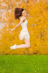 Beautiful young girl in white dress jumping on the background of